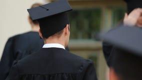 Giovani allegri in abiti accademici e cappucci pronti per graduation stock footage