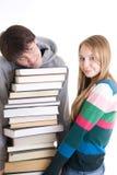 Giovani allievi di accoppiamenti con un mucchio dei libri isolati Fotografia Stock Libera da Diritti