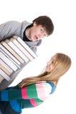 Giovani allievi di accoppiamenti con un mucchio dei libri isolati Fotografia Stock