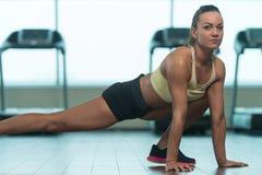 Giovani allungamenti della donna di forma fisica al pavimento Fotografie Stock
