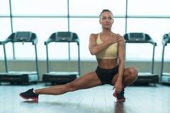 Giovani allungamenti della donna di forma fisica al pavimento Fotografie Stock Libere da Diritti