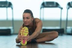 Giovani allungamenti della donna di forma fisica al pavimento Fotografia Stock
