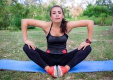 Giovani allungamenti della ragazza di forma fisica mentre allenamento Immagine Stock Libera da Diritti