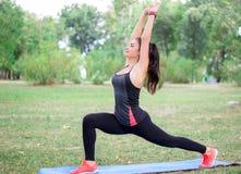Giovani allungamenti della ragazza di forma fisica mentre preparando allenamento Immagini Stock