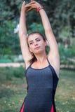 Giovani allungamenti della ragazza di forma fisica mentre si preparano risolva Fotografia Stock Libera da Diritti