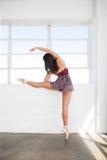 Giovani allungamenti lei stessa della donna del ballerino vicino alla finestra Fotografia Stock Libera da Diritti
