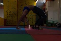 Giovani allungamenti sportivi della donna di misura Immagine Stock
