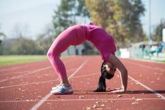 Giovani allungamenti sportivi della donna di misura Fotografia Stock