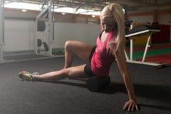 Giovani allungamenti sportivi della donna di misura con il rullo Fotografie Stock Libere da Diritti