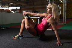 Giovani allungamenti sportivi della donna di misura con il rullo Fotografia Stock