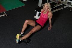 Giovani allungamenti sportivi della donna di misura con il rullo Immagine Stock