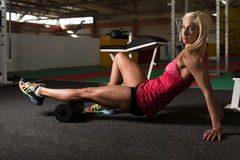 Giovani allungamenti sportivi della donna di misura con il rullo Fotografia Stock Libera da Diritti