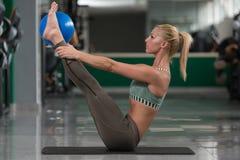Giovani allungamenti sportivi della donna di misura con la palla Fotografia Stock