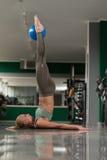 Giovani allungamenti sportivi della donna di misura con la palla Immagini Stock