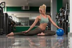 Giovani allungamenti sportivi della donna di misura con la palla Fotografie Stock