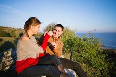 Giovani amanti allegri, tramonto sopra il mare, montagne, divertimento/porcile Immagine Stock