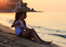 Giovani amanti che si siedono nella sabbia sulla riva Immagine Stock Libera da Diritti
