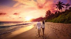 Giovani amanti felici sul tramonto della spiaggia fotografia stock