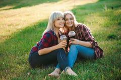 Giovani amiche che abbracciano al parco che si siede sull'erba immagine stock