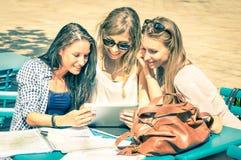 Giovani amiche dei pantaloni a vita bassa che studiano insieme e che si divertono Fotografia Stock