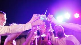 Giovani amichevoli che tostano con il night-club dei cocktail all'aperto stock footage