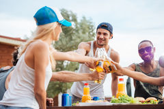 Giovani amici allegri che bevono birra e che celebrano all'aperto Fotografia Stock