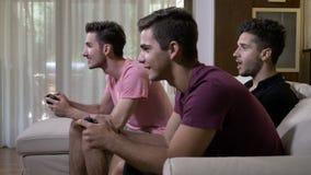 Giovani amici allegri che spendono tempo a casa che si siede sullo strato che mangia popcorn e che gioca i video giochi sulla con video d archivio