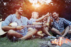 Giovani amici allegri divertendosi dal fuoco di accampamento Fotografie Stock Libere da Diritti