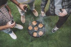Giovani amici che bevono birra e che fanno barbecue Immagini Stock Libere da Diritti