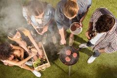 Giovani amici che bevono birra e che preparano carne sulla griglia all'aperto Immagine Stock
