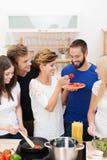 Giovani amici che cucinano insieme cena Fotografia Stock Libera da Diritti