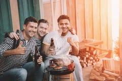 Giovani amici che fanno barbecue e che bevono birra sul portico con luce posteriore Fotografie Stock