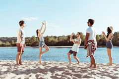 Giovani amici che giocano pallavolo sulla spiaggia sabbiosa al giorno Fotografia Stock Libera da Diritti