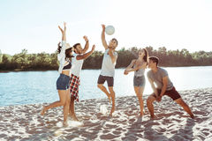Giovani amici che giocano pallavolo sulla spiaggia sabbiosa al giorno Immagini Stock Libere da Diritti