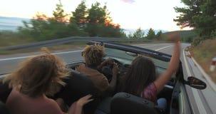 Giovani amici che godono del loro viaggio stradale in automobile convertibile video d archivio