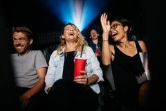 Giovani amici che guardano film della commedia sul teatro fotografia stock