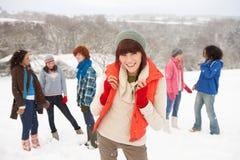 Giovani amici che hanno divertimento nel paesaggio dello Snowy Fotografie Stock Libere da Diritti