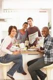 Giovani amici che preparano prima colazione in cucina fotografia stock