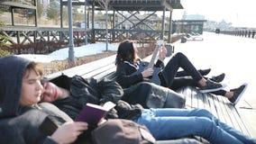 Giovani amici che raffreddano su un banco - due tipi che leggono un libro - un uomo che sintonizza la sua chitarra e la sua amica archivi video