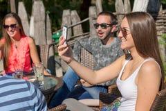 Giovani amici che ridono e che prendono immagine all'aperto Fotografie Stock