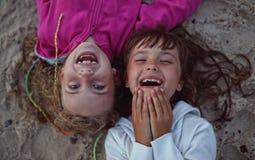Giovani amici che ridono mentre trovandosi fotografia stock