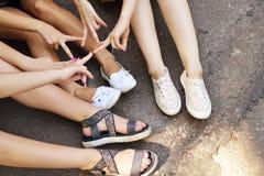 Giovani amici che si siedono sulla terra di estate Gambe delle ragazze Fotografia Stock