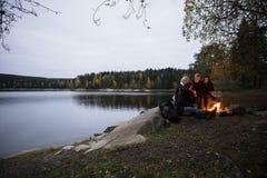 Giovani amici che si siedono vicino al falò dal lago al crepuscolo immagine stock libera da diritti