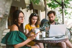 Giovani amici con gli smartphones ed il computer portatile in caffè con caffè Immagine Stock Libera da Diritti
