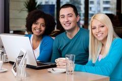 Giovani amici con il computer portatile in caffè Fotografie Stock
