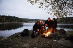 Giovani amici con le tazze di caffè che si siedono vicino al fuoco di accampamento fotografie stock