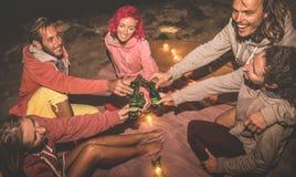 Giovani amici dei pantaloni a vita bassa divertendosi insieme al partito della spiaggia di notte fotografia stock