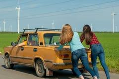 Giovani amici dei pantaloni a vita bassa sul viaggio stradale su un'automobile Immagini Stock Libere da Diritti