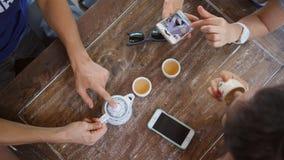 Giovani amici della corsa mista che bevono tè cinese in caffè e che per mezzo degli aggeggi del telefono cellulare 4K archivi video