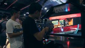 Giovani amici della corsa mista che giocano Arcade Shooter Game Machine nel centro commerciale di zona MBK del gioco 4K Bangkok,  stock footage